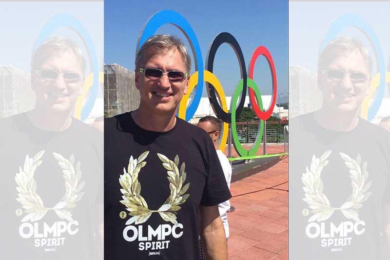 Imagem de Paulão do Vôlei, que foi Medalhista de ouro olímpico, em frente a um monumento com o símbolo das Olimpiadas ou seja, dos cinco anéis coloridos (azul, preto, vermelho, amarelo e verde), entrelaçados. este monumento simboliza a união dos continentes em prol do esporte.