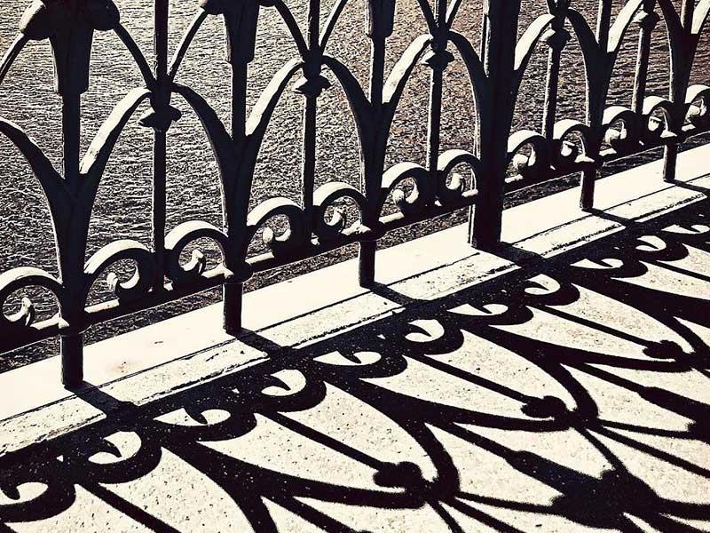 O rendilhado formado por uma grade de ferro bem trabalhada e sua sombra compõem uma imagem cheia de detalhes de curva e retas em A grade e a sua sombra - foto poesia para começar bem a semana