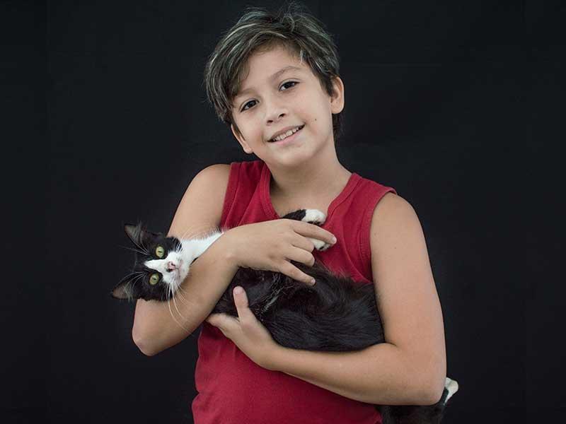 Um menino de dez anos,  camiseta vermelha e sorriso no rosto, traz um gato preto e branco carinhosamente aninhado em seu colo. O menino e o gato, compõem a imagem do Feita a felicidade felina - foto poesia para começar bem a semana
