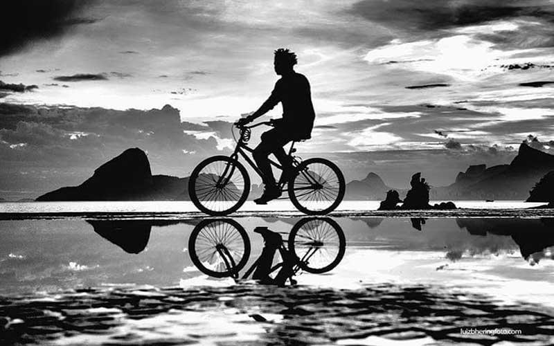 Imagem em preto e branco com um belo jogo de luzes. Traz a silueta de um rapaz passeando de bicicleta às margens da baia de Guanabara, no Rio de Janeiro. São as muitas e diferentes nuvens iluminadas no céu que dão intensidade e movimento à foto, acompanhadas pelas silhuetas do rapaz na bicicleta e pedras e morros do Rio de Janeiro como o Pão de Açúcar e o Corcovado. Um espelhamento de tudo isso é criado por uma grande poça na imagem de Bicicleta - foto poesia para começar bem a semana
