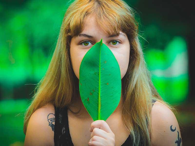 Jovem mulher de olhos verdes, camiseta preta e cabelo louro olha diretamente para o fotógrafo. A atitude de cobrir a sua boca e nariz com uma folha tão verde como os seus olhos compõe a imagem de O olhar - foto poesia para começar bem a semana