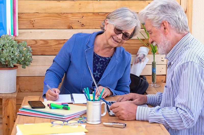 Um casal de meia idade sentado à mesa conversa sobre um texto de interesse comum. Ela segura um caderno, ele um computador. Muitos materiais de escritorio ajudam na conformação de um cenário de um cenário de produção literária.