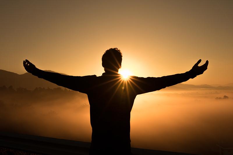 Silhueta de um jovem que celebra o nascer do sol do alto de uma montanha e de braços abertos. Predomina na foto, a cor de laranja e alguns tons de marrom. O sol brilhante tem destaque especial para insicar que felizes são aqueles que...