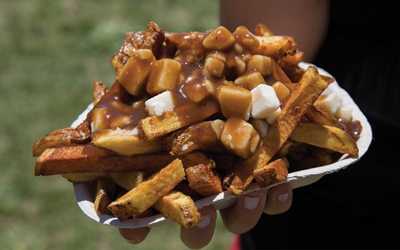 Imagem com uma porção de Poutine, um prato típico canadense de receita simples. A base do Potine é batata frita recoberta com molho de carne e pedacinhos queijo chedar branco ou de queijo coalho.