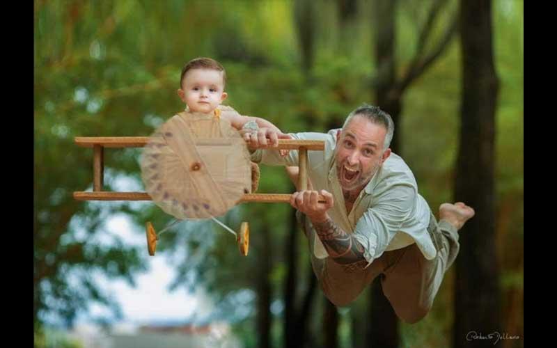 """Na imagem da poesia Aviãozinho do amor, pai e filho se divertem juntos. A atmosfera é de amor, confiança e simplicidade. O pai, empurra um aviazinho artesanal de madeira, que tem,  como  """"piloto."""", o filhinho de dois anos,"""