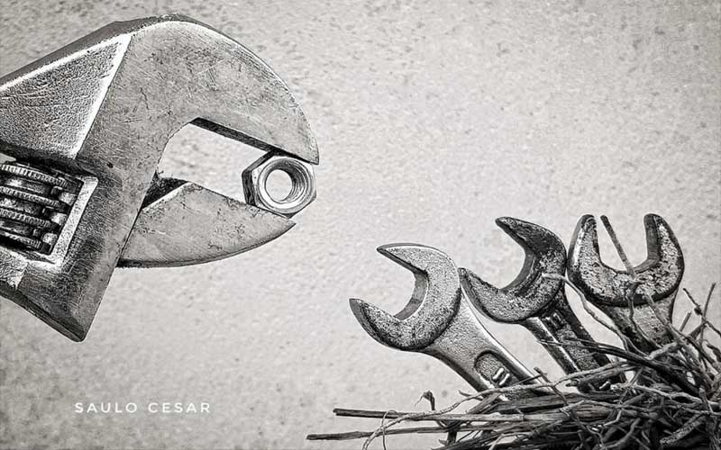 Uma chave inglesa que agarra uma porca se parece com uma ave que chega ao ninho com alimento. Á direita, um conjunto de tres chaves de boca pequenas em um ninho de palha representam os filhotinhos que , de boca aberta, aguardam ser alimentados nesta imagem de O mundo mecânico - foto poesia para começar bem o dia