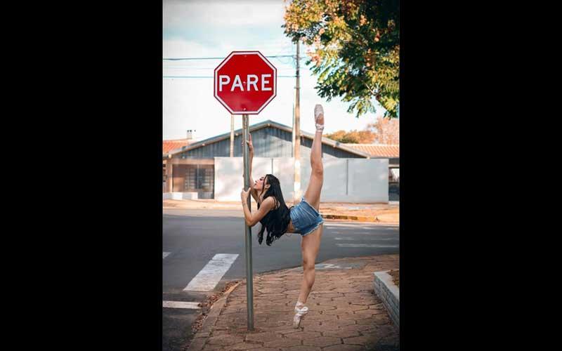 Uma mulher de short jeans azul e blusa preta, em pose de bailarina, apoia-se no poste de uma placa vermelha de sinal `PARE` e alinha as suas pernas verticalmente em180 graus (posição de espacato do ballet clássico) em perfeito paralelismo com o poste. Esta é a imagem de A placa - foto poesia para começar bem a semana