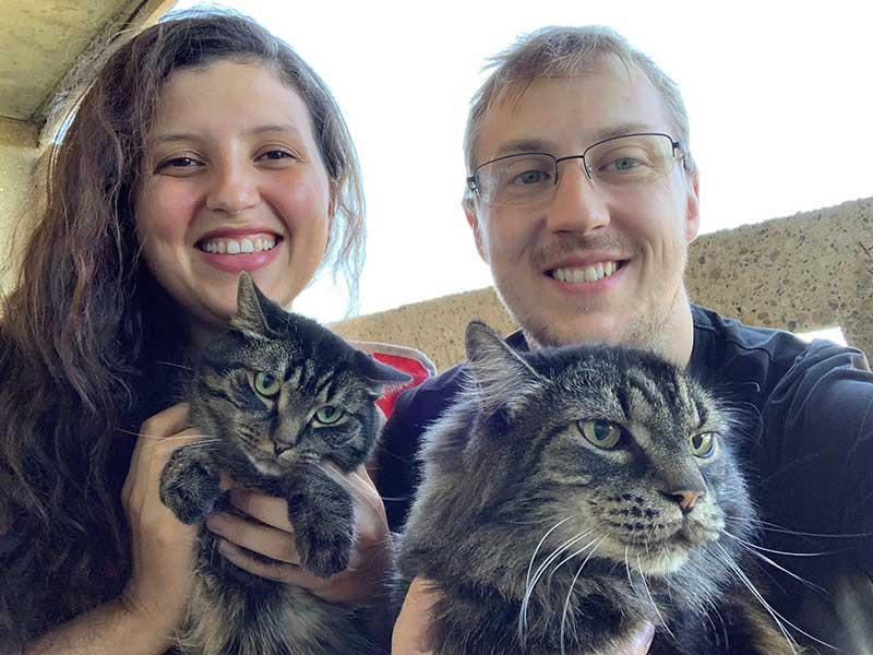 O casal Jéssica Chaves Cardoso, brasileira, e Justin Gage, canadense, com os gatos Maya e Hobbes no colo, indicando que também os gatos sofrem com a atual onda de calor no oeste do Canadá.